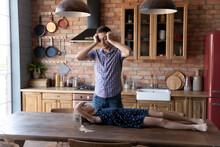 Funny Daddy And Little Daughter Girl Playing Active Game In Kitchen, Going To Prepare Dinner. Naughty Kid Turning Dad From Cooking, Lying And Resting On Kitchen Table Top. Family Entertainment Concept