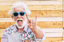 Crazy Nice Old Senior Man Expression Portrait With Colorful Clotehs - Concept Of Rebel No Limit Age And Youthful People - Caucasian Elderly Male With White Beard And Hair Do Rock'n Roll Sign