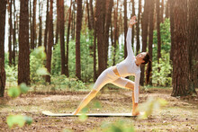 Young Attractive Female Wearing White Sportswear Doing Yoga Practice On Beautiful Nature In Forest, Young Adult Female With Perfect Body In Triangle Pose.