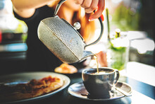 Woman Hand With Metal Teapot Pour Black Tea In Black Glass Cup In Cafe