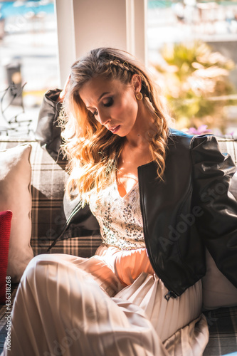 Fotografija Beautiful young blond Caucasian woman on the sofa of the hotel where she is staying on vacation