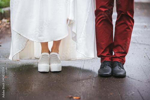 Canvas Feet of the bride and groom on the wet asphalt