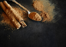 Aromatic Cinnamon Scattered On A Black Background. Powder And Cinnamon Sticks