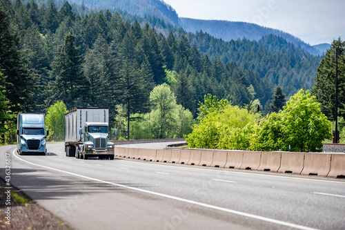 Fototapeta Two different big rig semi trucks with semi trailers running side by side on the