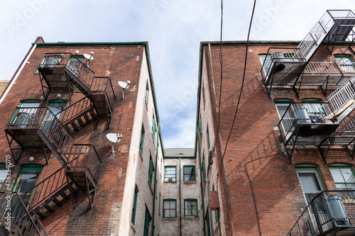 Fototapeta Centered view of a light well between apartment building wings, metal fire escap