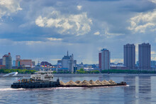 A Barge Loaded With Building Materials Moves Along The Amur River.