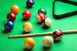 Leinwandbild Motiv Many colorful billiard balls and cue on green table