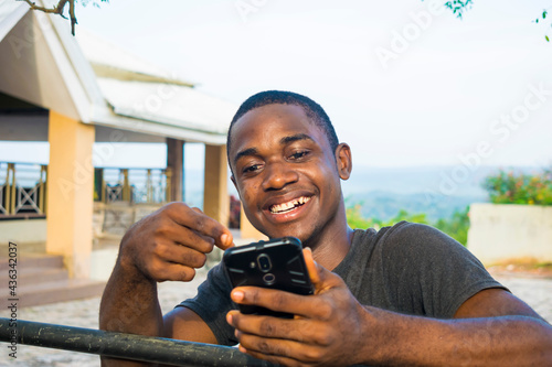 Excited african american millennial Young man hold smartphone feel euphoric read Fototapet