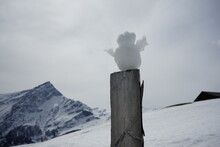 Snowman On A Pole In The Swiss Snow Covered Mountains