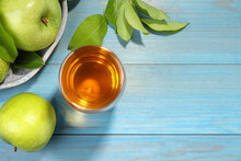 Glass Of Fresh Juice And Apples On Light Blue Wooden Table, Flat Lay. Space For Text