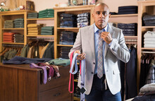 Portrait Of Male Client Of Mens Clothing Boutique Choosing And Trying On Necktie