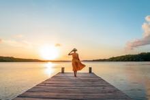Woman Walking Along The Pier At Sunset