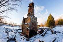 Remains Of A Burned Down House With A Brick Oven In The Middle Of A Snowy Nature, A Chimney On The Ashes