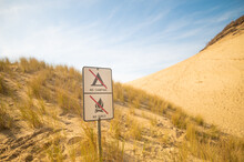 In The Photo We See The Desert. Mountainous Terrain. Grass Scorched By The Sun Grows On The Side Of The Mountain. Prohibitory Signs. No People. Color Image.