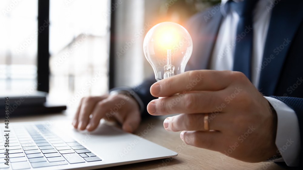Leinwandbild Motiv - fizkes : Business leader working on new startup idea of saving energy solution, developing innovative project. Male professional working at laptop and holding shining lightbulb. Innovation concept. Close up
