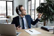 Excited Happy Funny Businessman In Wireless Headphones Listening To Music, Enjoying Favorite Song, Playing Air Guitar, Pretending To Be Guitarist, Rock Star, Relaxing And Having Fun During Work Break