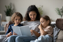 Caring Young Latino Mom And Two Small Kids Rest On Couch At Home Reading Interesting Book Together, Loving Happy Hispanic Mother And Little Children Enjoy Literature Story On Lazy Family Weekend.