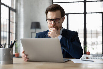 Thoughtful serious businessman reading email message on laptop screen, thinking over problem solving and making decision, watching online video conference or learning webinar, analyzing market