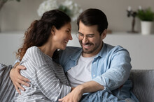 Smiling Young Multiethnic Couple Sit Rest On Couch At Home Hugging And Embracing Enjoy Romantic Weekend At Home. Happy Multiracial Man And Woman Relax On Sofa In Living Room. Family Concept.