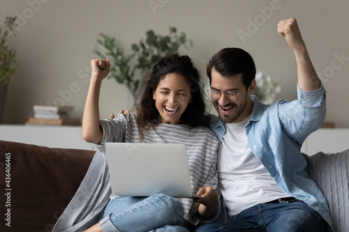 Excited multiethnic couple feel euphoric win online lottery win or victory on laptop gadget Fototapeta