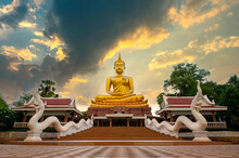 Beautiful  Big Golden Buddha Statue Against Sunset Sky In Thailand Temple,khueang Nai District, Ubon Ratchathani Province, Thailand.Amazing Buddha Image With Sunny Sky Clouds.