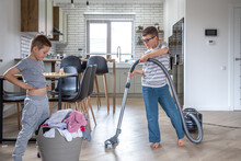 Two Little Boys Help With The Laundry And Cleaning Of The House.