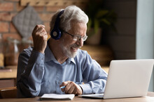 Grey Haired Elderly Man Sit Indoors Wear Headphones Looks At Laptop Screen Holding Pen Gain New Knowledge Use Web Resources And Internet Connection. On-line Counselling Services, Modern Tech Concept
