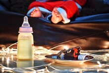 Baby Sleeping After Christmas Celebrations. Milk Bottles And Cakes Are Also Seen In The Photo. High Quality Photo