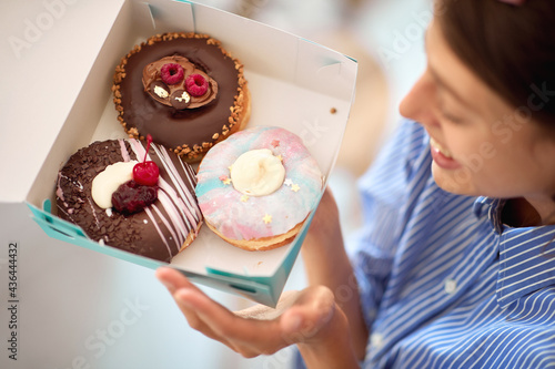 Obraz na płótnie A beautiful girl in a pastry shop is passionately looking at a box with delicious donuts she holds in her hands