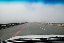 View From Inside A Car Of A Road On A Bridge In South Africa, Leading Into A Cloud, Covering The End Of The Bridge