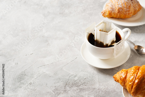 Billede på lærred Cup of coffee with drip filter and croissant