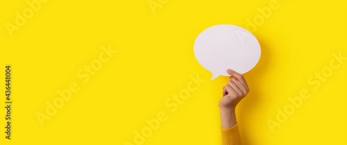 Fotografia bubble speech layout in hand over yellow background, panoramic mock-up