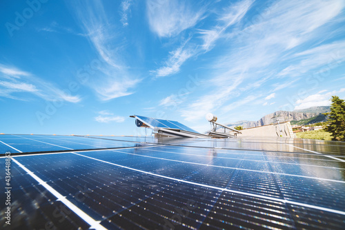 Fotografiet Renewable energy system with solar panel for electricity and hot water