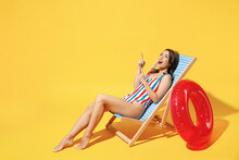 Full Body Length Happy Young Sexy Woman Wear Striped Red Blue One-piece Swimsuit Sit On Wooden Chair Isolated On Vivid Yellow Color Wall Background Studio. Summer Hotel Pool Sea Rest Sun Tan Concept.