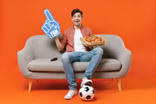 Young Man Football Fan In Shirt Support Team With Soccer Ball Sit On Sofa At Home Watch Tv Live Stream Hold Pizza Fan Foam Glove Finger Isolated On Orange Background People Sport Lifestyle Concept