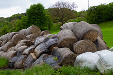 Rolled Up Hay Bales Wrapped In A Net And Piled Up To A Heap