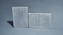Studio Shot Of Two Pairs Of Sterling Silver Jewelry Dangle Earrings On Concrete Elements Isolated Over Gray Background