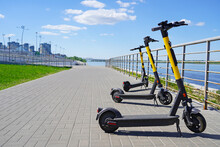 Yellow And Black Electric Scooters For Rentare Parked On The Embankment Against The Background Of The River And Blue Sky