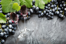 Two Wine Glasses Filled With Wine Lying In Frame Made Of Grapes. Black Juicy Grapes Red Wine On Vintage Dark Concrete Background. Copy Space On Black Scuffed Background. Border