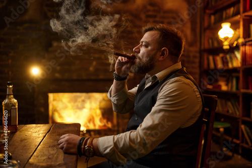 Fotografia Man smokes a cigar and drinks alcohol beverage