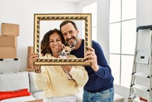 Middle Age Hispanic Family Smiling Happy Holding Empty Frame At New Home.