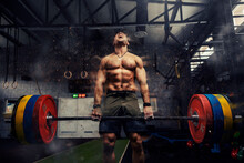 Weightlifter In The Gym, Visual Effects Of Positive Energy On Training. Strong Attractive Man Holds A Heavy Barbell In His Hands And Lifts A Weight In A Modern Gym Concept. Screaming During Exercises