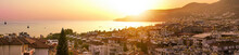 Panoramic Landscape - Alanya Turkey Resort Town In Orange Sunlight At Sunset. Sunny City Landscape Top View. Natural Panorama Of Beautiful Mountains And Sea At Sunset.