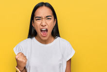 Young Asian Woman Wearing Casual White T Shirt Angry And Mad Raising Fist Frustrated And Furious While Shouting With Anger. Rage And Aggressive Concept.