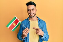 Young Arab Man Holding Suriname Flag Smiling Happy Pointing With Hand And Finger