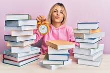 Young Caucasian Woman Holding Alarm Clock Sitting On The Table With Books Looking At The Camera Blowing A Kiss Being Lovely And Sexy. Love Expression.