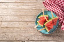 Watermelon Slices Popsicles On Blue Plate On Rustic Wooden Table. Top View. Copy Space