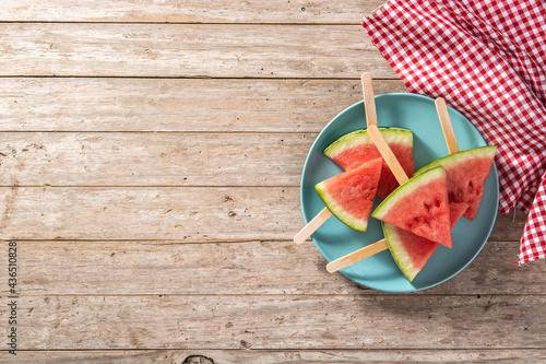 Obraz na plátně Watermelon slices popsicles on blue plate on rustic wooden table