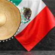 Leinwandbild Motiv Mexican flag and sombrero hat on dark background