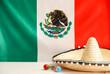 Leinwandbild Motiv Sombrero hat and maracas on table against Mexican flag